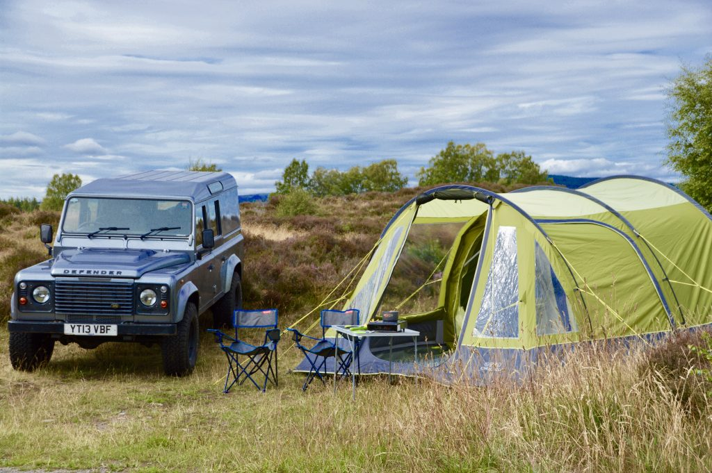 Defender next to our largest 5 person family tent
